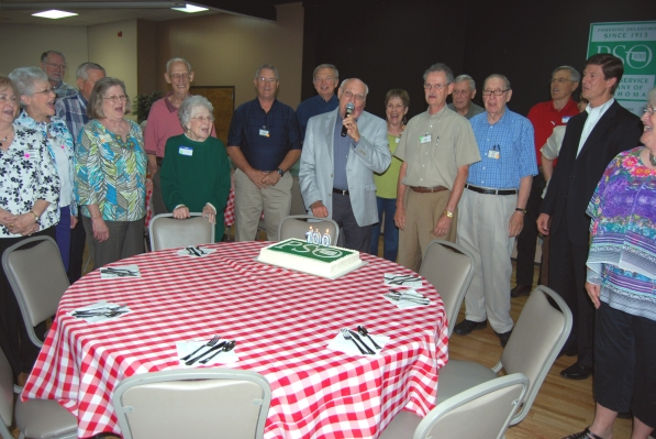 "Public Service Company of Oklahoma (PSO) retirees led by Ron Scott (holding the microphone) gather around a birthday cake and join PSO President Stuart Solomon (second from right) in singing ""Happy Birthday"" in honor of PSO's upcoming Centennial May 29. PSO's birthday ""salute"" was part of the Tulsa Circuit Riders annual spring picnic, held May 22 at the Green Country Event Center in east Tulsa."