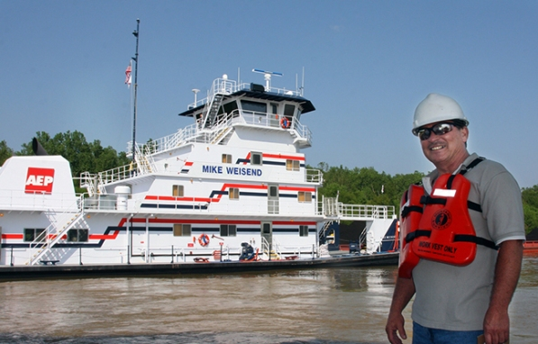 Mike Weisend (right), manager of safety and health for AEP River Operations, stands across from his namesake, the M/V Mike Weisend towboat. The vessel will be on display at two upcoming river festivals in West Virginia and Ohio.