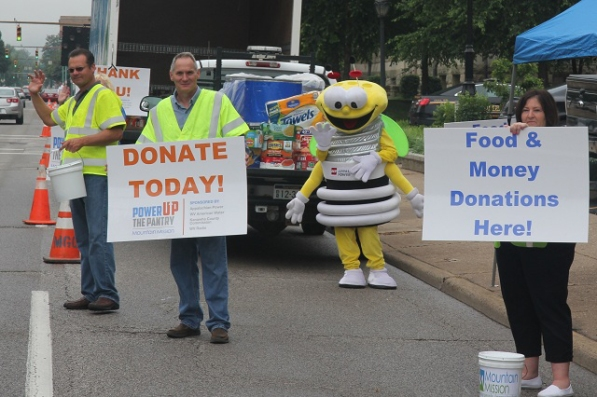 "John Workman (left), distribution line coordinator, and Roger Blankenship (center), IT field manager, volunteered to help with the ""Power up the Pantry"" fundraiser. Kathleen Cowan, daughter of Dan Cowan, customer services engineer, made an appearance as Louie the Lightning Bug."