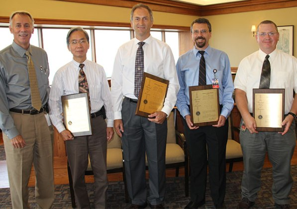 Mark McCullough (far left), executive vice president - Generation, congratulates a team of AEP engineers who were awarded a U.S. patent for the Large Particle Ash Mitigation System. Shown are (left to right): Chao Lin, Jeff Hofacre, Tom McCartney and Darren Hanby. Not shown: Jim Silk.