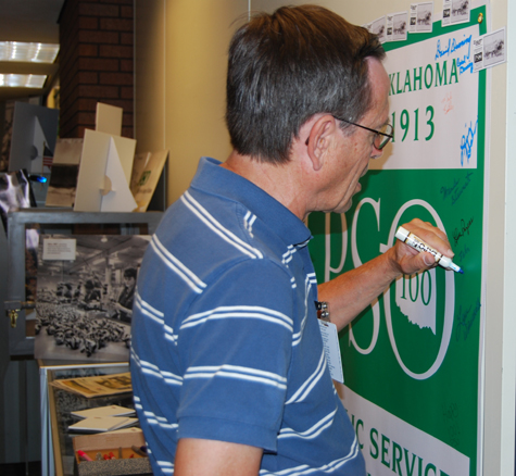 Retiree John Rittenoure adds his name to the PSO Centennial banner on display in the General Office first floor archives area.
