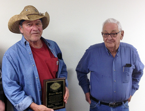 Bruce Martin (left), recently retired serviceman in Chouteau, holds a plaque presented to him by Mayor Jerry Floyd during the March 10 Chouteau Town Council meeting.