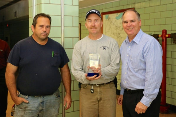 Travis Woods (left) and Greg Cook (holding the crystal award) are shown with Nick Akins, AEP chairman, president and chief executive officer. Akins made a surprise visit to the Clinch River Plant to present the pair with one of the corporation's highest safety awards for employees. Photos by John Shepelwich.