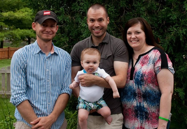 Tony Fosler (center) holds his son, Elias, as his wife, Amber, looks on. AEP employee Zac Netherton (left), Tony's cousin, donated part of his liver to Elias.