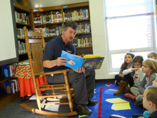 Jim Cook, director of transmission region construction for AEP, reads to students at Breckinridge Elementary School in Fincastle, Va.