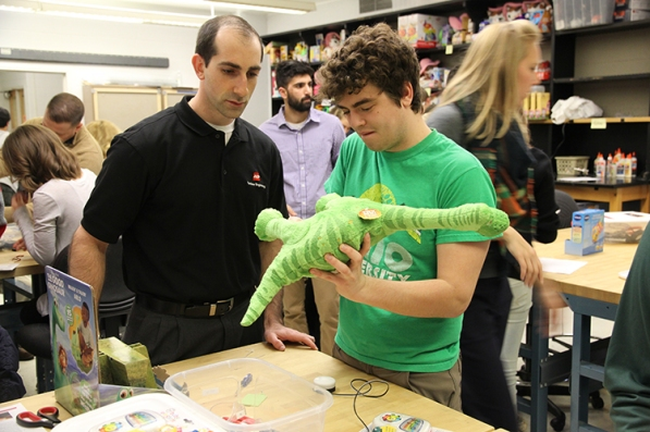AEP's John Garlitz (left) and a student partner figure out how to take apart a talking dinosaur toy.